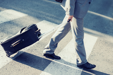 Elegant businessman walking with suitcase outside airport. Banque d'images