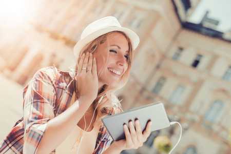 Young attractive woman is smiling while wearing headphones.