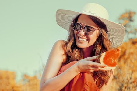美麗的年輕女子在公園裡吃西瓜。 版權商用圖片
