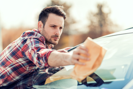 Young man cleaning his car outdoors.Man with a microfiber wipe the car polishing. Фото со стока