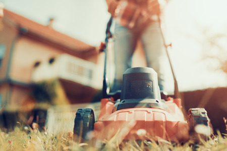 Man cutting grass in his yard with lawn mower. Banco de Imagens