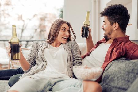 年輕夫婦在客廳坐在床上,一起玩樂。