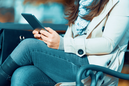 Young woman using her digital tablet outdoors.