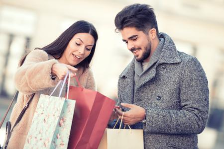 夫婦愉快的購物袋在城市。 版權商用圖片