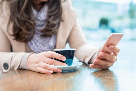 在咖啡館關閉的女人喝咖啡了。 版權商用圖片
