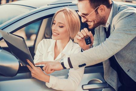 Car dealership.Young woman receiving car key from salesman. Banco de Imagens