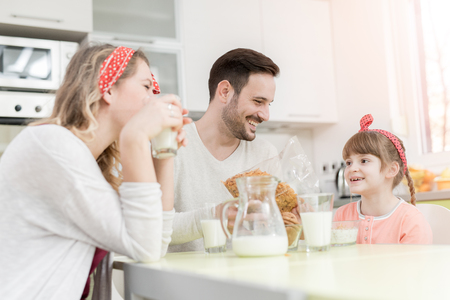 Portrait of happy family having breakfast together at home Archivio Fotografico