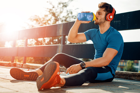 Portrait of young man drinking some water from a bottle while sitting and resting after training. Banco de Imagens