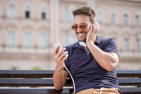 Individuo hermoso sonriente escuchar música en la ciudad. Foto de archivo
