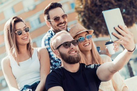 Friendship, summer,technology and people concept - smiling friends making selfie outdoors.