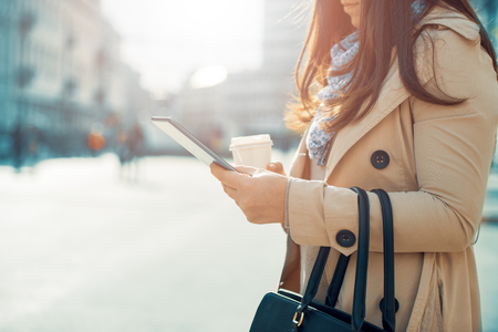 Young woman in the street drinking morning coffee and use her smart phone.