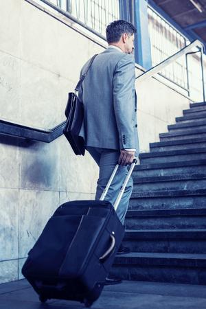 jetsetter: Elegant businessman walking with suitcase outside airport. Stock Photo
