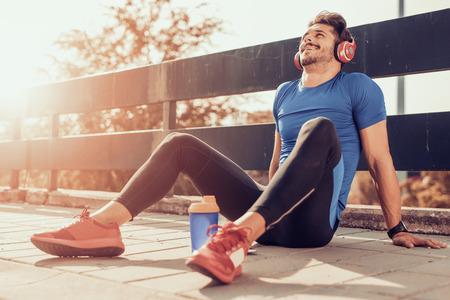 Jonge mannelijke joggeratleet die en training in openlucht in stad opleidt doet.