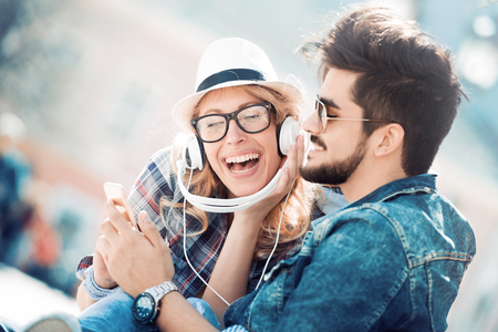 Happy couple with headphones sharing music from a smart phone on the street. Stock Photo