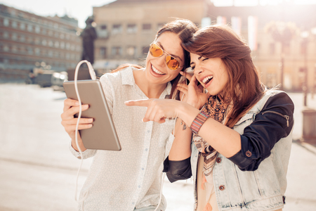 Friends  listening to music on a smart phone in the city.