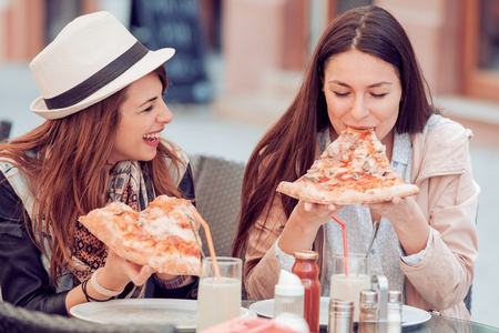 Two cheerful  girls eating pizza in a outdoor cafe. Banco de Imagens