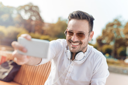 Young attractive man is smiling while wearing headphones in the city.