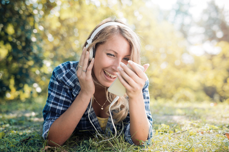 hands free phone: Young woman listening to music on a smart phone outdoors. Stock Photo