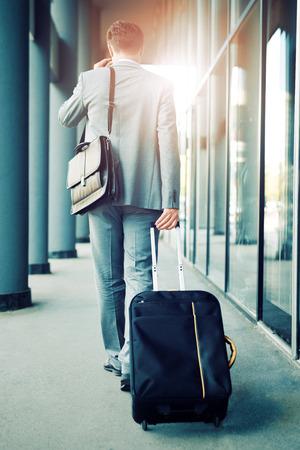 Elegant zakenman lopen met koffer luchthaven buiten.