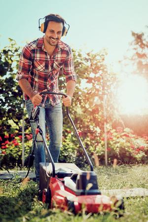 Man snijden gras in zijn tuin met grasmaaier.
