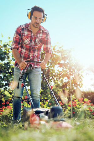 Man cutting grass in his yard with lawn mower. Stock Photo
