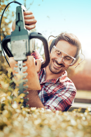 Young gardener with a professional garden tools at work. Stock Photo