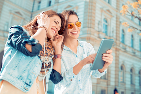 Two young beautiful girls are walking through the city and listening to music. Stock Photo