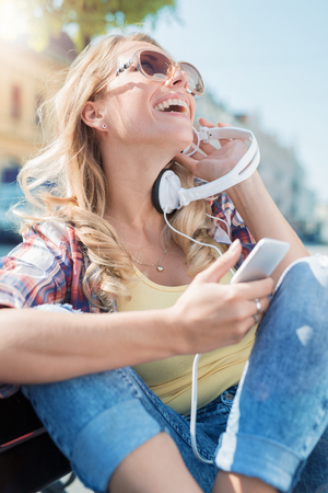 Young woman listening to music on smart phone outdoors. Stock Photo