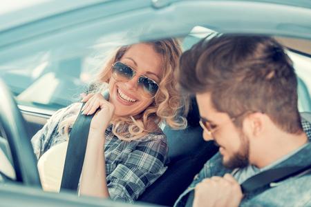 Jonge man en vrouw glimlachen terwijl ze zitten in een nieuwe cabriolet.