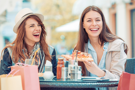 Two smiling girls eating pizza in cafe,taking break after good shopping. Stockfoto