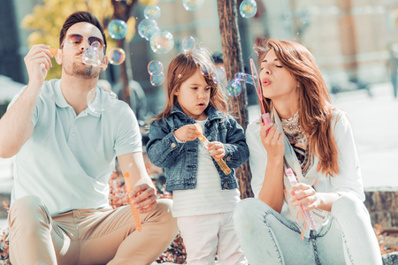 Young family having fun with daughter blow soap bubbles. Stockfoto