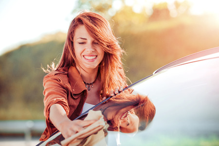 Young woman cleaning her car outdoors.Transportation self service, care concept. Stockfoto