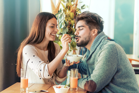 Happy young couple having breakfast in cafe,enjoying together. Stockfoto