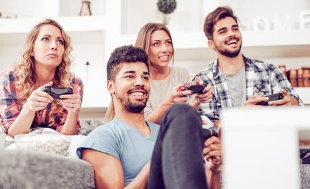 Groep vrienden spelen van videospellen thuis.