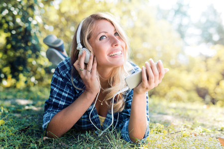 Young woman listening to music on a smart phone in the park. Stockfoto