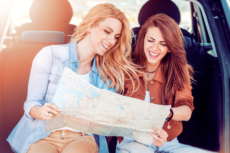 Two young girls going to travel by car,sitting in car trunk and holding map. Stockfoto