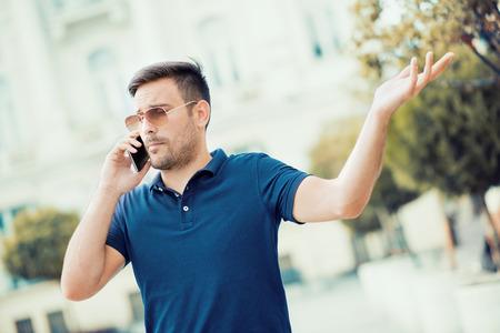 Jonge stedelijke professionele man met behulp van slimme telefoon.