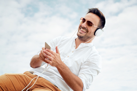 Close up of handsome young man smiling while listening to music. Banque d'images