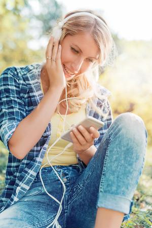 Knappe jonge vrouw genieten van muziek op een zomerdag in het park.