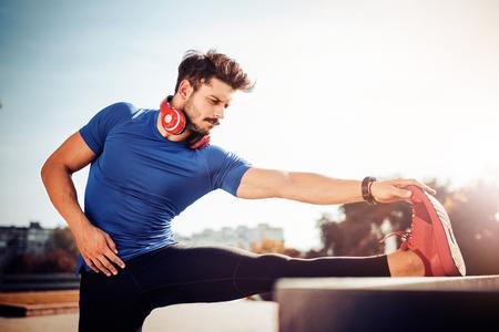 Jonge mannelijke jogger atleet opleiding en training in openlucht in stad.