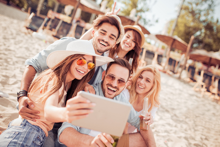 Summer,holidays,vacation and happiness concept-group of friends taking selfie.
