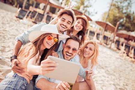 Zomer, vakantie, vakantie en geluk concept-groep vrienden die zelfie nemen. Stockfoto