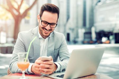 Zakenman surfen op internet op zijn laptop in de stad.