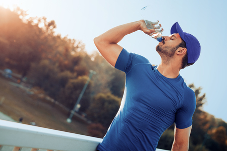 Portrait of young man drinking some water from a bottle after training.