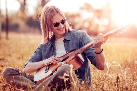 Oefen in het spelen van gitaar. Knappe jonge mannen die gitaar spelen.