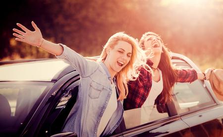 Twee gelukkige vrouwelijke vrienden genieten van de wegreis Stockfoto