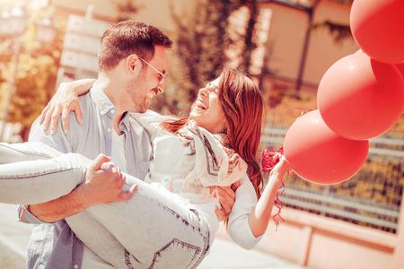 Счастливый молодая пара, с удовольствием на открытом воздухе и улыбается.
