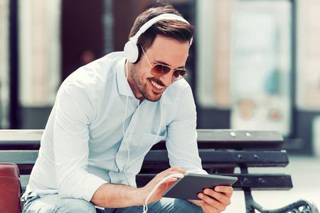 Knappe jonge man luisteren naar muziek in de stad.