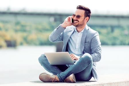Knappe jonge man met behulp van laptop in het park op een zomerdag.