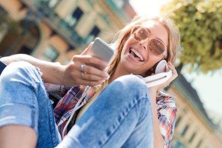 Jonge vrouwen met behulp van slimme telefoon, luisteren naar muziek op een zomerdag in de stad. Stockfoto